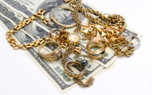 Various gold jewelry items sitting atop $100 bills.