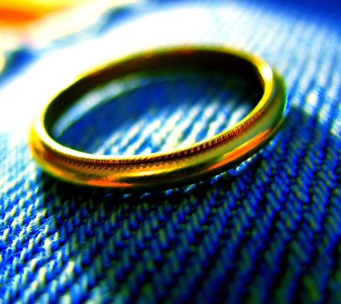 a plain gold ring on a blue fabric