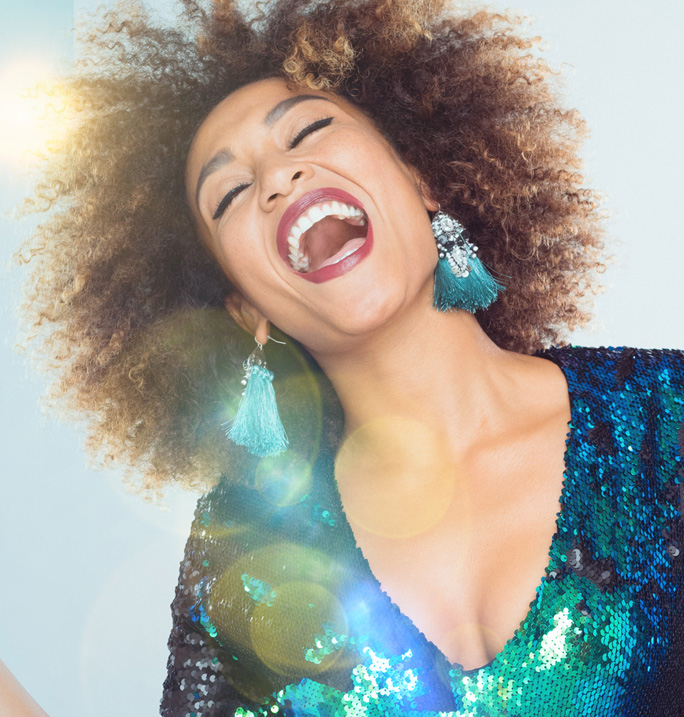 Happy woman in sparkly dress is ready to celebrate the new year. Click here for information about our New Year's Sale 2019.