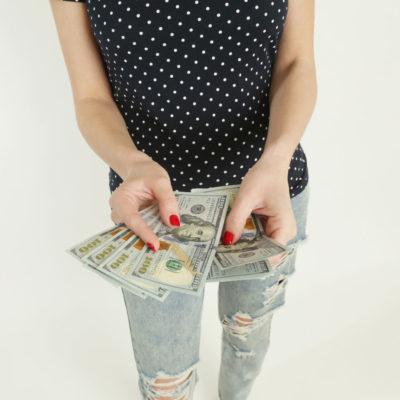 A woman holding several 100 dollar bills.