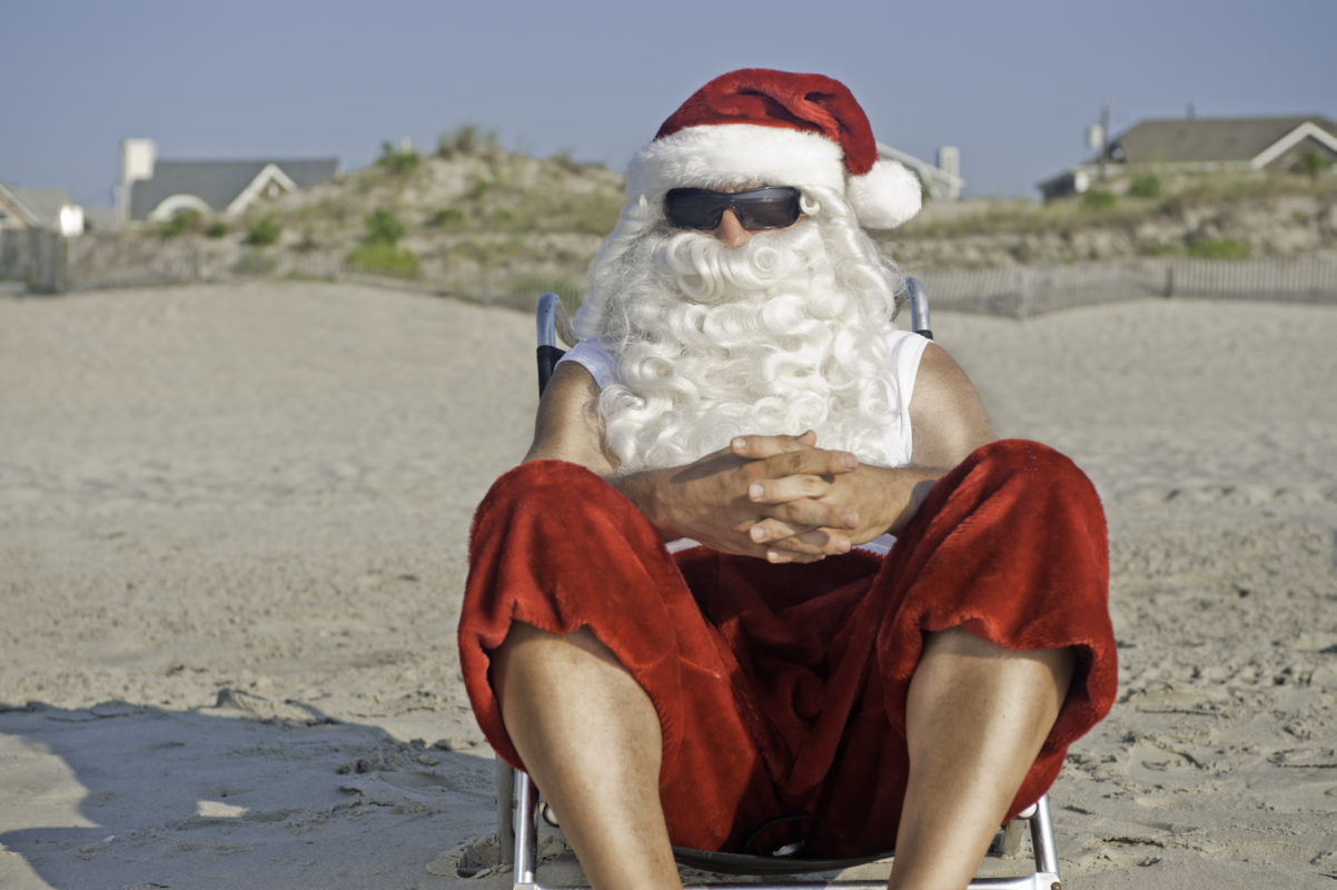 Christmas in July: Santa Claus on vacation relaxing at the beach