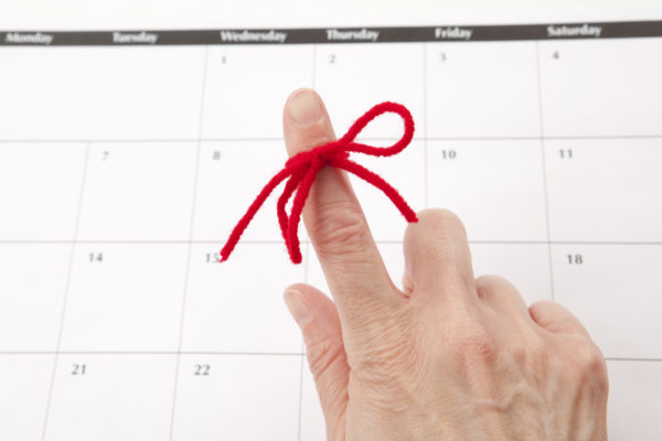 A red string tied around an index finger in front of a calendar: email alerts remind customers when their loans are due