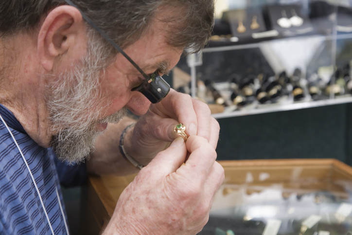 History of pawn shops: A man appraising jewelry.