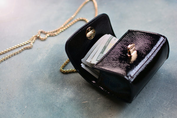Opened fashion women's handbag stuffed with dollars lying on the floor. Cash For Luxury Handbags